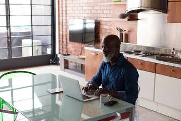 Senior man using laptop in kitchen