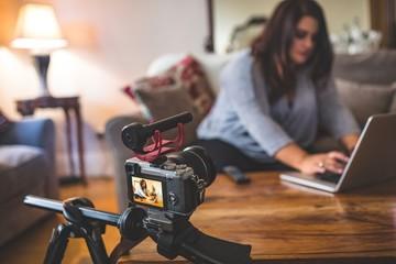 Female vlogger sitting on sofa while using laptop