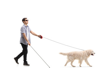 Blind young man walking with the help of a dog