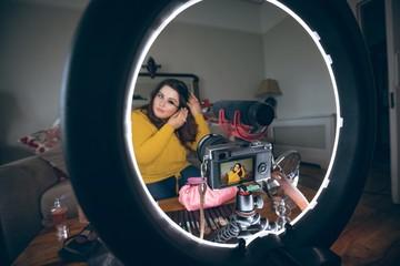 Beautiful female vlogger applying mascara
