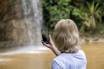 Woman tourist standing near waterfall and making picture on smart phone.Woman making selfie near waterfall.Vacation,holiday concept.