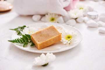 beauty, spa, body care, bath and natural cosmetics concept - close up of handmade soap bars on white table
