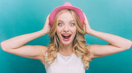 Very exited girl is looking straight forward and holding her pink hat with hands on a head. She is surprised a lot. Isolated on blue background.