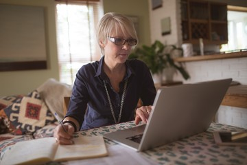 Mature woman using laptop while writing in diary