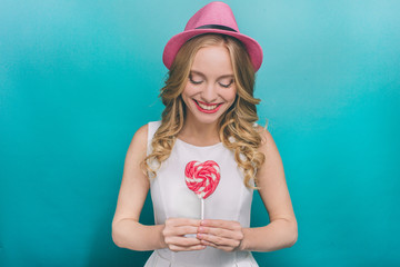 Happy young woman is wearing pink and holding a pink lollipop in her hands. It has a heart shape. She is looking at it and smiling. Isolated on blue background.