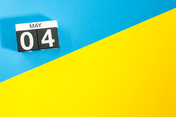 May 4th. Day 4 of may month, calendar on blue and yellow background flat lay, top view. Spring time. Empty space for text