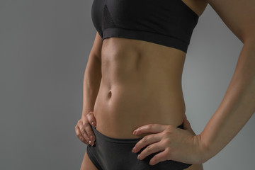 Portrait of a female figure, tightened sexy sports belly