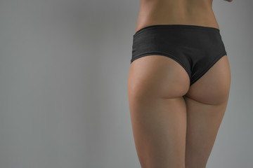 A sporty ass girl on a gray background. Sports figure