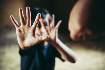 Furious man raised punishment fist over scared child, trafficking concept and illegal labor