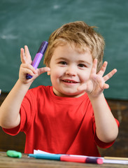 Toddler cute and cheerful ready to study. Kid boy in classroom near colorful markers, chalkboard on background, close up. Arts and stationery concept. Child drawing in school, kindergarten.