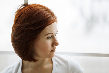 Portrait of a sad woman sitting near window. Unhappy woman with brown hair looking aside. Depression and bad feelings concept