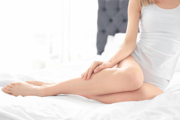 Young woman showing smooth silky skin after epilation on bed at home