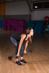 Muscular young fitness woman doing deadlift exercise in gym