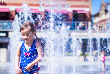Cute Little Girl in Blue Swimming Suit Playing with Water jets of Street Fountain, Hot Summer Day, Kids Fun, in England, Dorchester