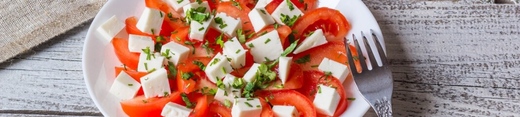 Banner of Fresh salad with tomato, mozzarella and herbs.