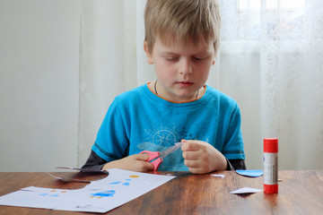 Cute little kid cutting colored paper with scissors at home