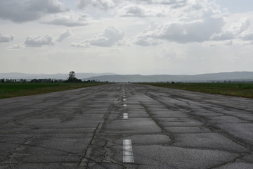Abandoned runway used as rally racetrack. Cracks and car tire tracks seen on the wet after the spring rain asphalt surface.
