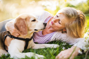 Beautiful senior woman with dog in spring nature.