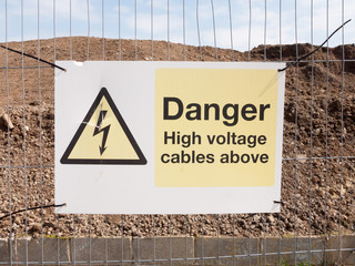 close up construction site fence sign: danger high voltage cables above