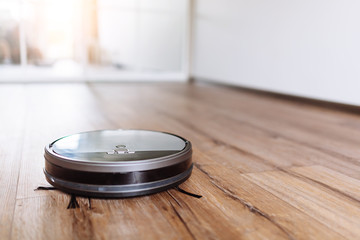 Robotic vacuum cleaner on laminate wood floor smart cleaning technology. Selective focus.