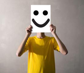 persona che tiene davanti al viso un foglio felice