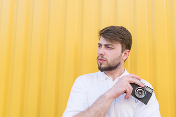 Portrait of a man with a retro camera in his hands on a yellow background. Hipsters poses with a melting pot on the background of a yellow wall