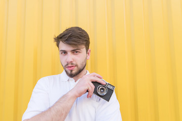 A handsome man holds a film camera in his hands and looks at the camera on the background of the yellow wall. Portrait of a man with retro hipster camera