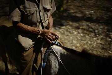 Hipolito Marrero, 83, smokes a cigar as he commutes on horseback in the mountains near Santo Domingo, Cuba