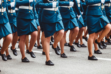 The women soldiers in blue uniform marching at a military parade