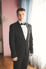 Beautiful man, groom posing and preparing for wedding
