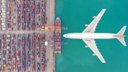 Container ships and transport aircraft in the export and import business and logistics international goods. Shipping cargo to harbor by crane. Aerial view and top view. Wall mural