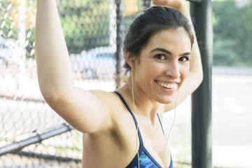 Portrait of fit young woman smiling while exercising in park
