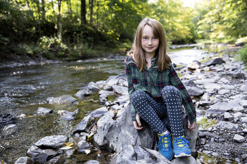 Portrait of cute girl smiling while sitting on rock by river in forest