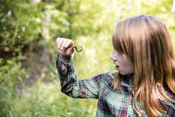 Closeup of little girl looking at earthworm on finger while exploring in forest