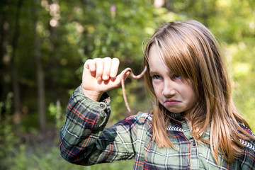 Cute little girl making face while holding earthworm