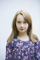 Portrait of cute girl with star sticker on face over white background