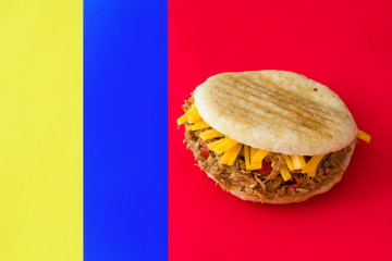 Arepa with shredded beef and cheese with colors of venezuelan flag. Venezuelan typical food