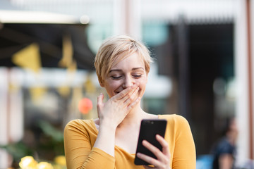 Young adult female laughing at smartphone