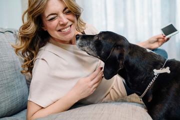 Pregnant woman on sofa petting dog