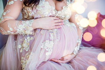 Beautiful pregnant girl in pink dress. Closeup of round tummy