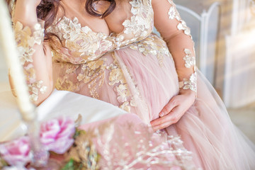 Pregnant girl in pink dress. Closeup of round tummy