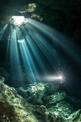 Male diver diving in underground river (cenote) with sun rays and rock formations, Tulum, Quintana Roo, Mexico