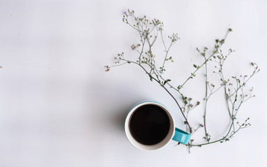 The ceramic coffee cup put beside flower,on white background.