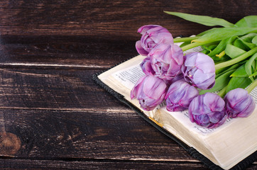 Violet tulips, book on wooden background. Vintage and retro style.