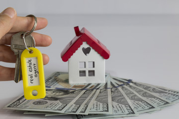real estate and mortgage investment. dollars and house and key on the white background.