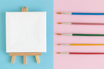 Blank art canvas on easel with multicolored paint brushes on pastel background