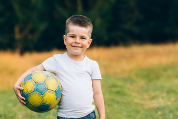 Child with a soccer ball under his arm at house garden with grass background, smiling. Kid Sport and Soccer World Cup Concept.