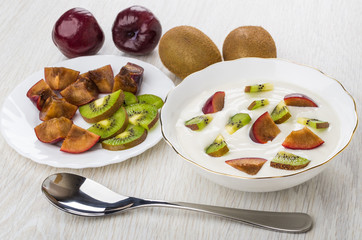 Cottage cheese with kiwi and plums in bowl, fruits, spoon