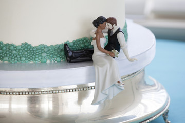 Cake topper on wedding cake featuring interracial couple.