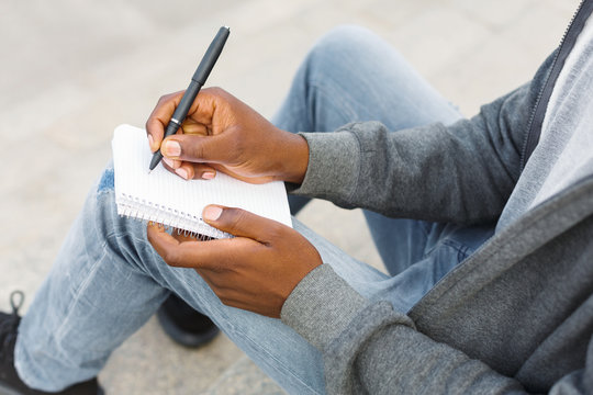 Young unrecognizable student making note